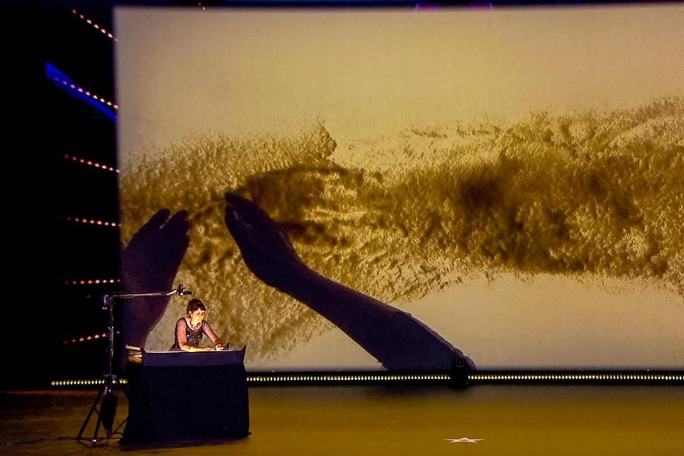 Tijdens de act creëert Colette een reeks van beelden via het aanbrengen van zand op een verlicht oppervlak.