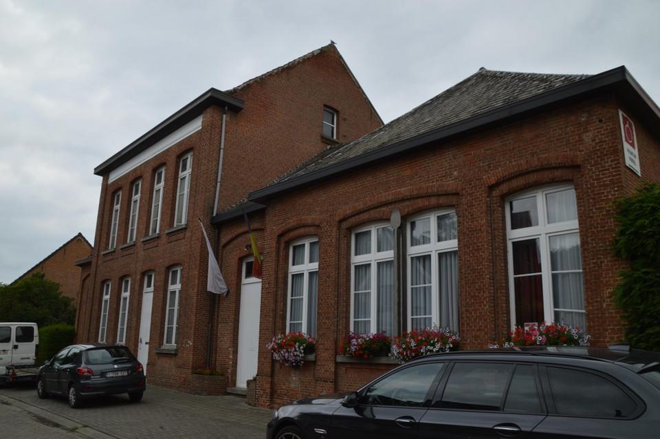 Het oud schoolgebouw met achterliggende chirolokalen.