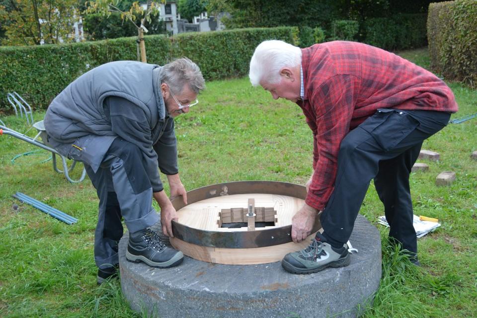 Louis De Pooter van de smedersgilde, rechts en Jan Nys van de Brakken (links) passen de ring vooraleer hem warmgestookt over de olmen ringen te kloppen.