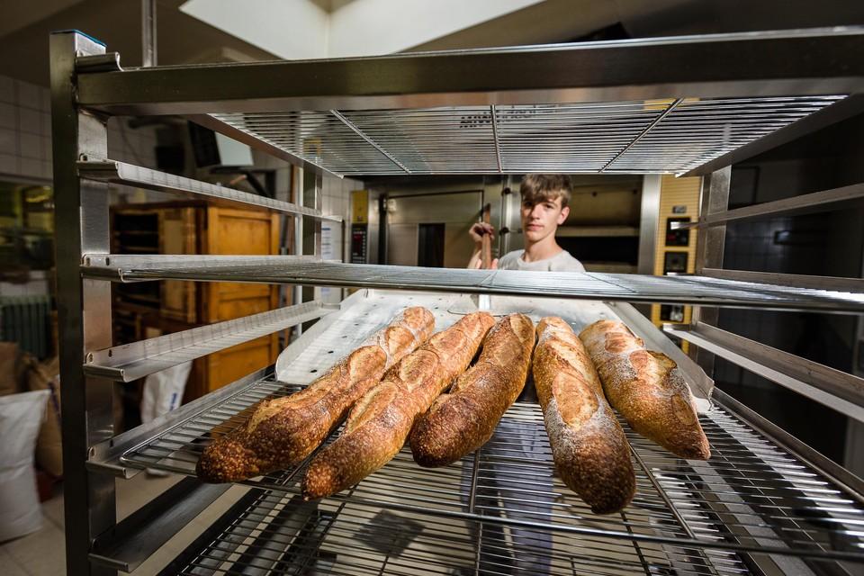 Bakker Viktor Fierens haalt versgebakken stokbroden uit de oven.