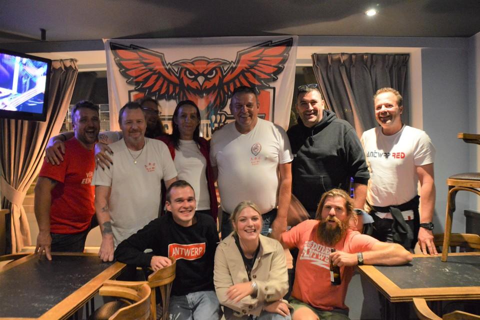 Enkele leden van ASC Rood Wit Legioen voor de vlag met bosuil van de RAFC-supportersclub in café De Patriot in Zandhoven. Tweede van links voorzitter François Nooytens en centraal cafébaas Rudi Bru.