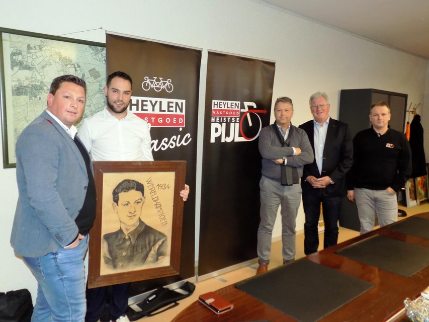 De organisatoren van de Heistse Pijl staan bij burgemeester Gilles Bultinck (CD&V). Hij toont een schilderij van Karel Kaers, de Vosselaarse wereldkampioen wielrennen in 1934.