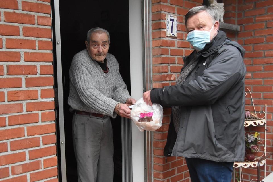 Fons Smets krijgt van vrijwilliger Stanny het gemeentelijke verrassingspakket met een broodje en een koffiekoek.