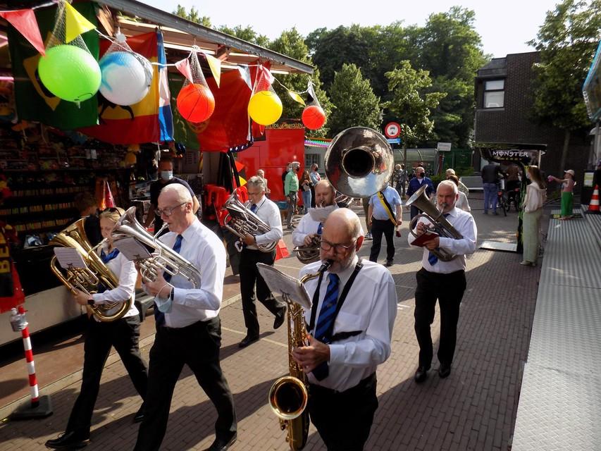Muzikanten van fanfare De Ware Vrienden stappen langs de kermiskramen in Vosselaar.