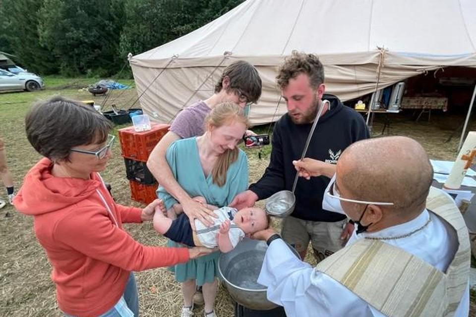 Pastoor Alvi doet met de pollepel het water over het hoofdje van Simon (of is het Lucas?) Ken en Bieke staan achter hun kindje.