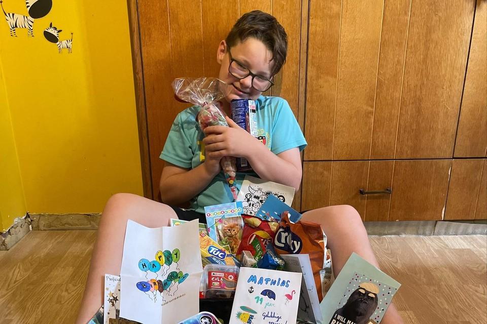 De jarige Mathias met kaartjes, tekeningen, snoepgoed en cadeautjes die hij kreeg na een oproep van zijn mama.