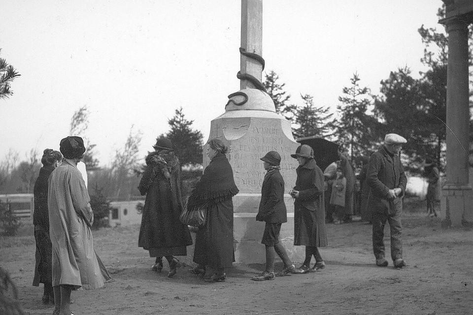 Bedevaarders wandelen rond het kruis bij de kapel in de eerste helft van de twintigste eeuw.