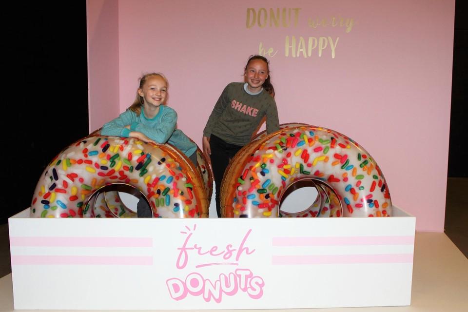 Lisse Vandevoort en Lotte Smet poseren tussen donuts.