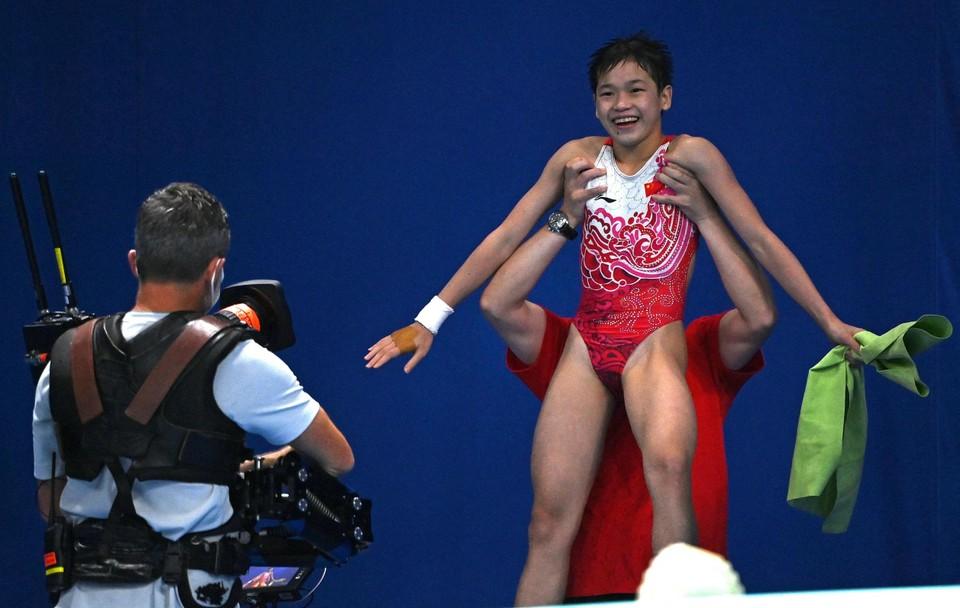 De amper 14-jarige Quan Hongchan wordt na drie quasi perfecte sprongen in de lucht gestoken door een van de Chinese coaches.
