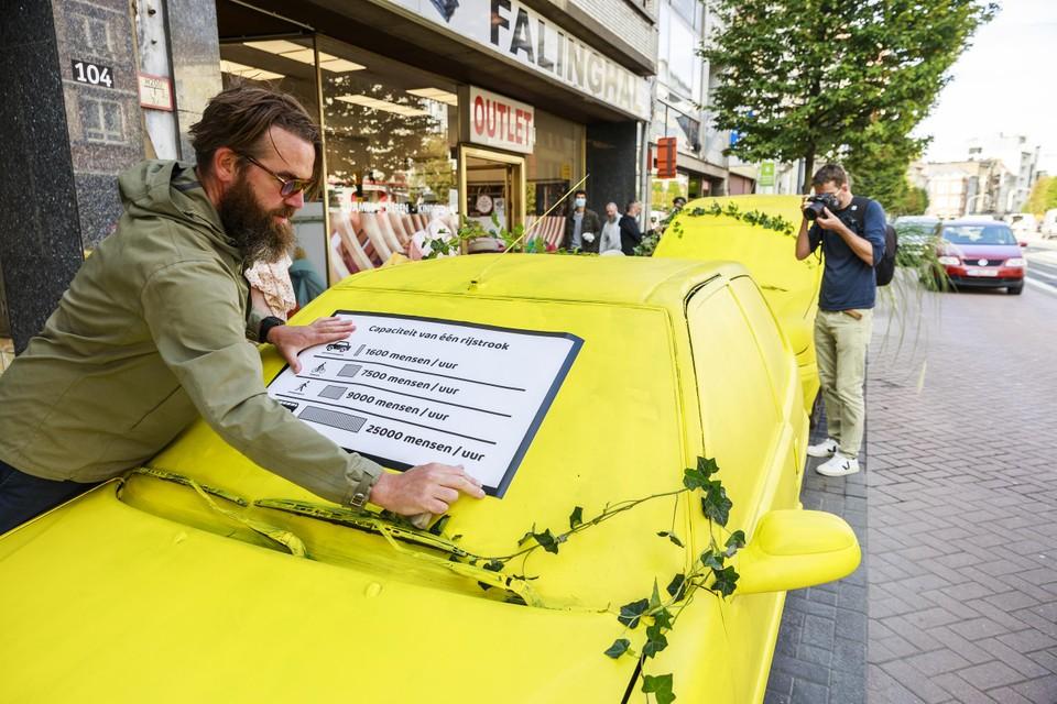 Fietsactivist Stijn Wens bevestigt een affiche op een van de beschilderde wagens op de Turnhoutsebaan. Die moet ons aan het denken zetten hoeveel ruimte wagens inpalmen in het straatbeeld.