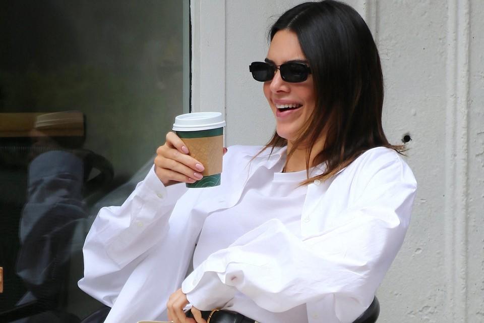 Kendall Jenner, met zonnebril op de neus, geniet van een terrasje met een koffie.