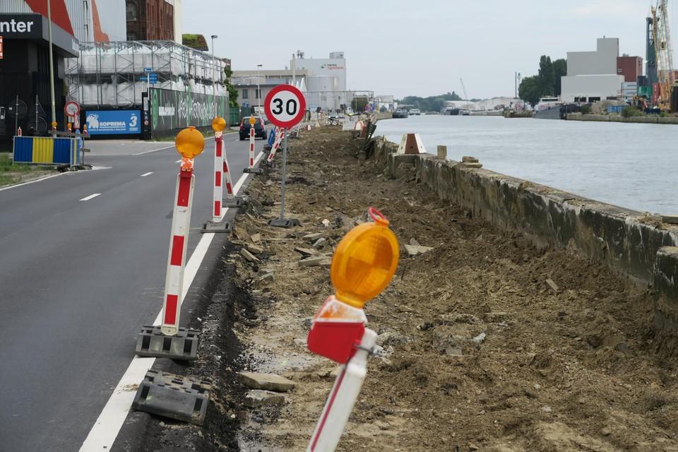 De werf is ingericht om de kaai langs het Albertkanaal te vernieuwen. De snelheidsbeperking wordt meermaals aangegeven.