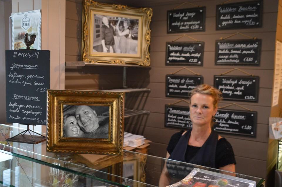 Sandy achter de toonbank, met vooraan een foto van haar en Ron in betere tijden.