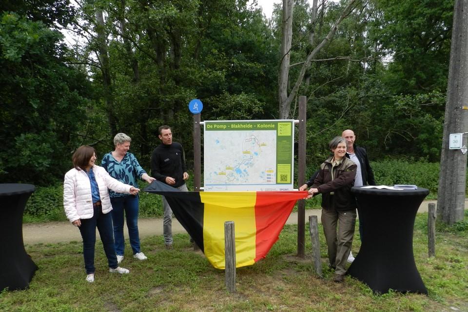 Vertegenwoordigers van de drie gemeenten, Sport Vlaanderen en ANB onthullen het infobord op het startpunt aan de parking Blakheide in Beerse.