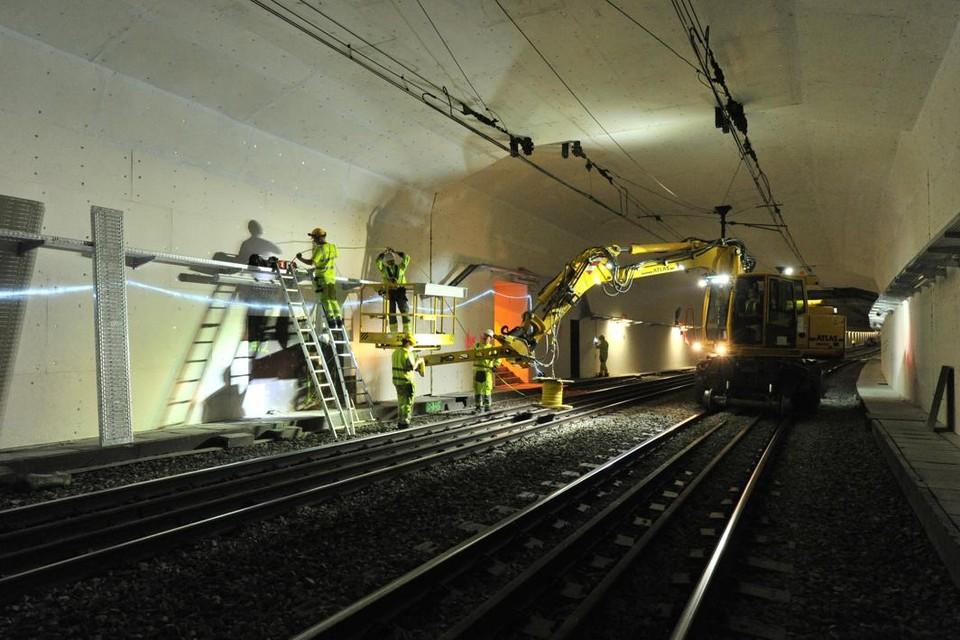 Technici installeren brandwerende panelen in de ruim vijftig jaar oude spoortunnel onder de Schelde in Antwerpen.