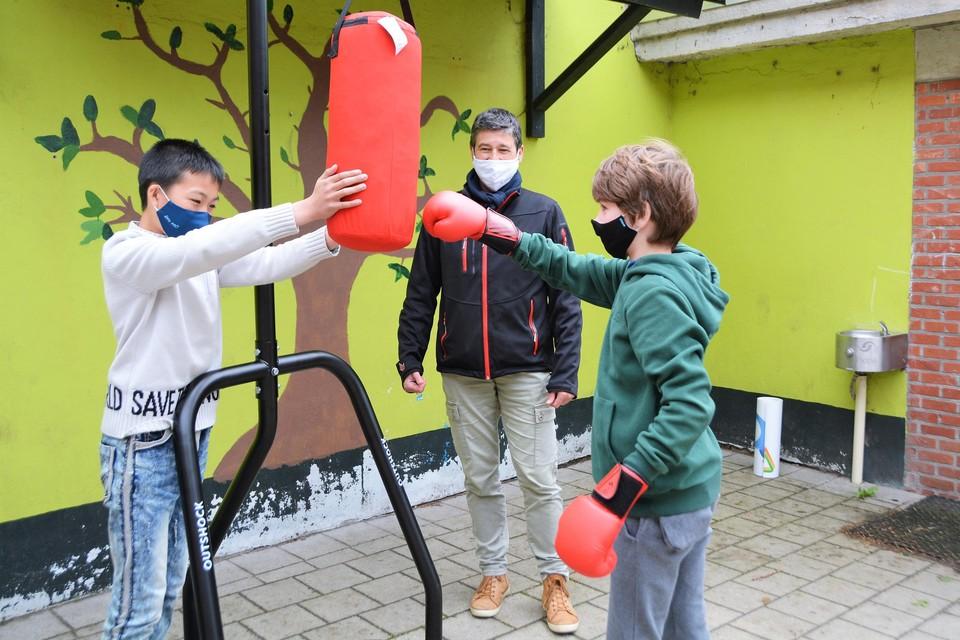 Terwijl Victor de boksbal ervan langs geeft, helpt zijn vriend Jeffrey door de boksbal stil te houden.