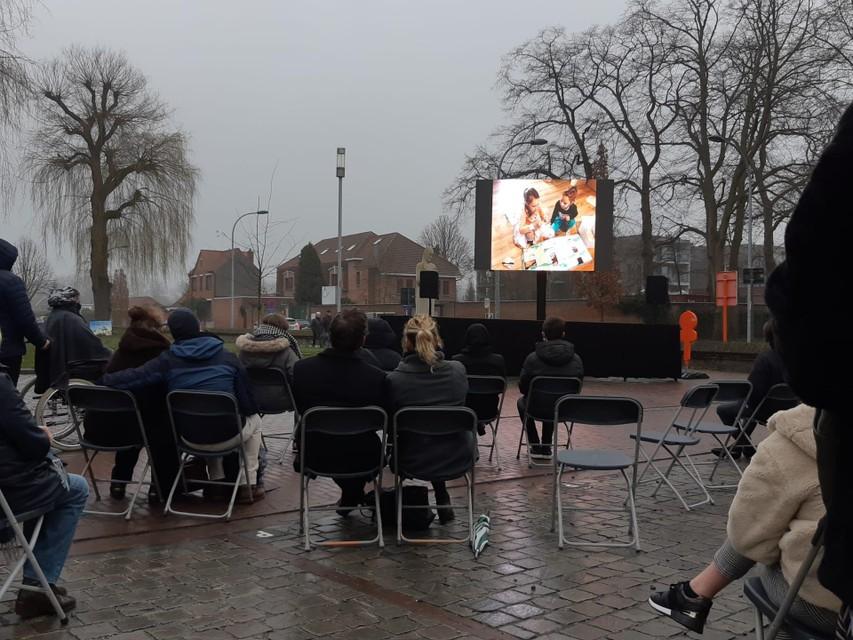 Een groot scherm buiten aan de kerk toont de uitvaart.