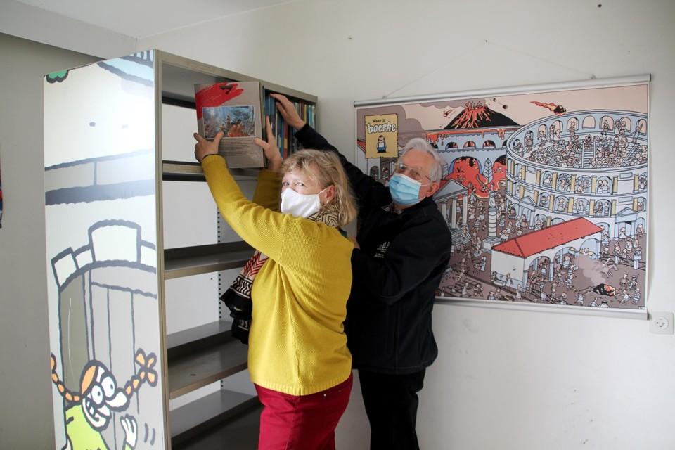 Vrijwilligers Chantal en Raymond vullen de nieuwe boekenrekken in de StripARK met strips.
