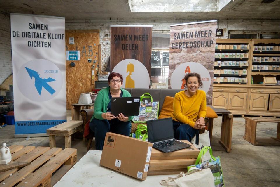 Schepenen Marina De Bie en Gabriella De Francesco bij Deelbaar Mechelen met enkele van de aangekochte laptops.