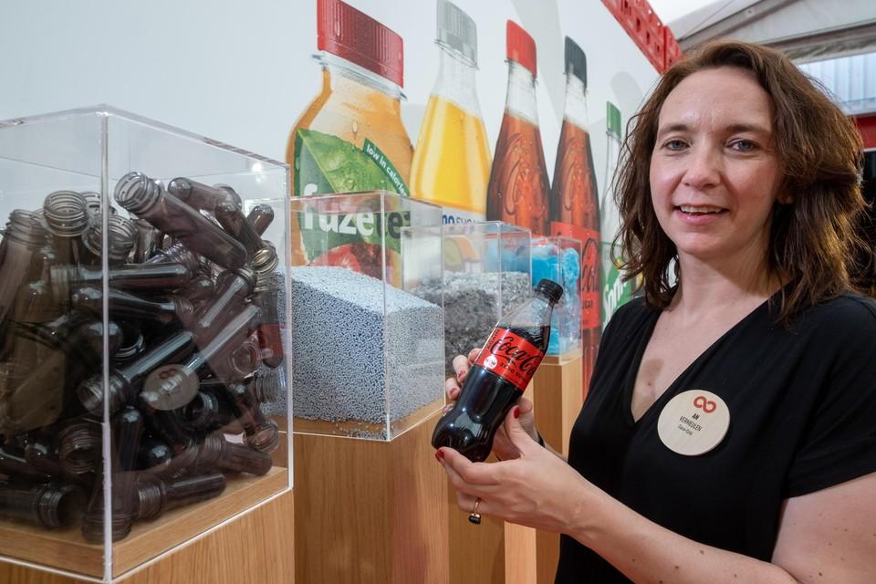 An Vermeulen, directeur van Coca-Cola in België, toont een flesje cola dat van gerecycleerd materiaal is gemaakt. In de bak links vooraan liggen de , de gerecycleerde basis waarvan de nieuwe flesjes worden gemaakt.