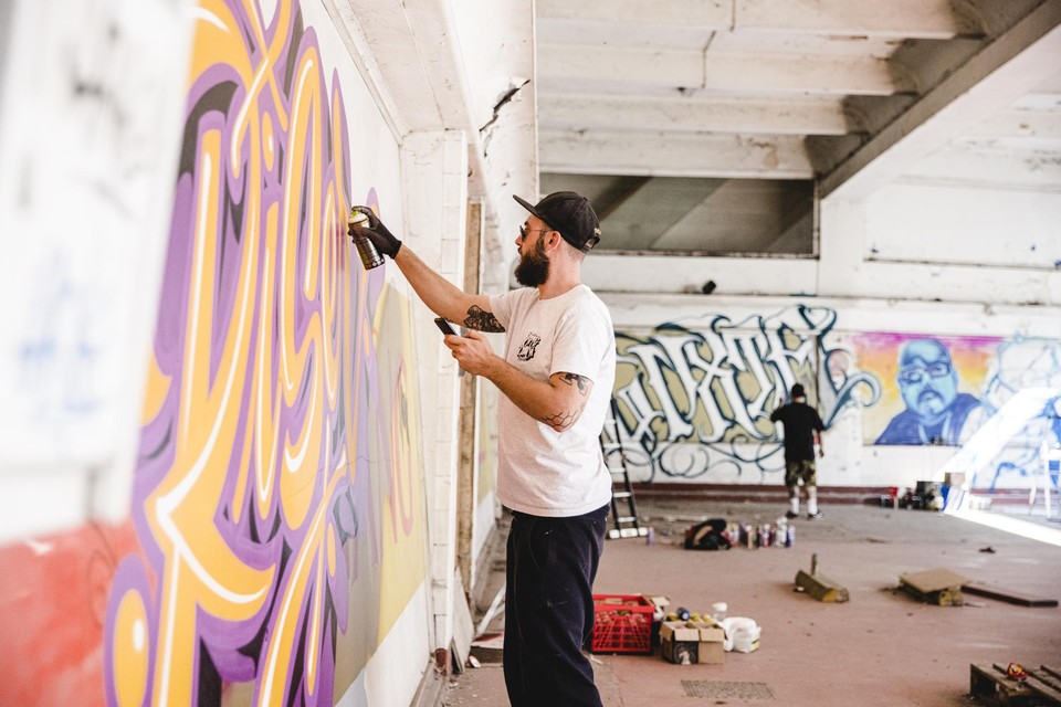 Graffitiartiest Yvon Tordoir van Aerosol Kings aan het werk op de Markgravelei.