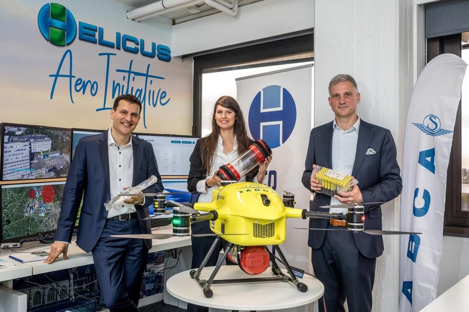 Deze gele drone zal in de komende jaren geneesmiddelen, bloed, urine en weefsel tussen Antwerpse ziekenhuizen vervoeren. Achter de drone staan Mikael Shamim (links) en Geert Van Handenhove (rechts) van de firma Helicus, die de vluchten coördineert, en Greet Ilegems (midden) van vliegtuigbouwer Sabca.