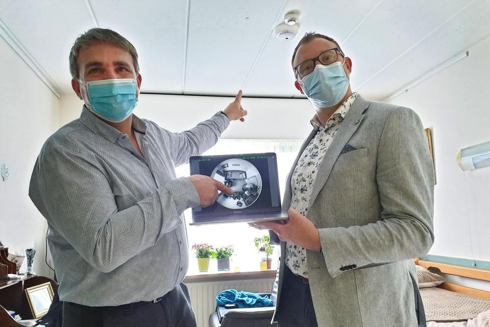 Schepen van Sociale Zaken Bert Vangenechten en Tim Beullens van Delta Care demonstreren hoe de slimme sensor werkt.