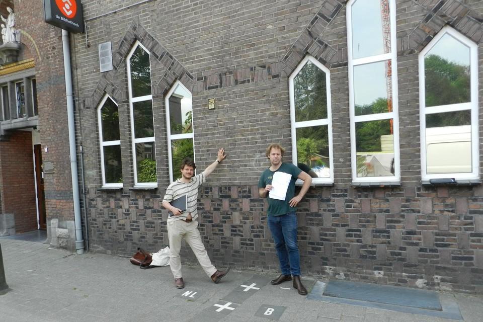 Paul Govaerts en Maarten Westra Hoekzema staan aan de grenslijn bij de ingang van het cultuurcentrum in Baarle.