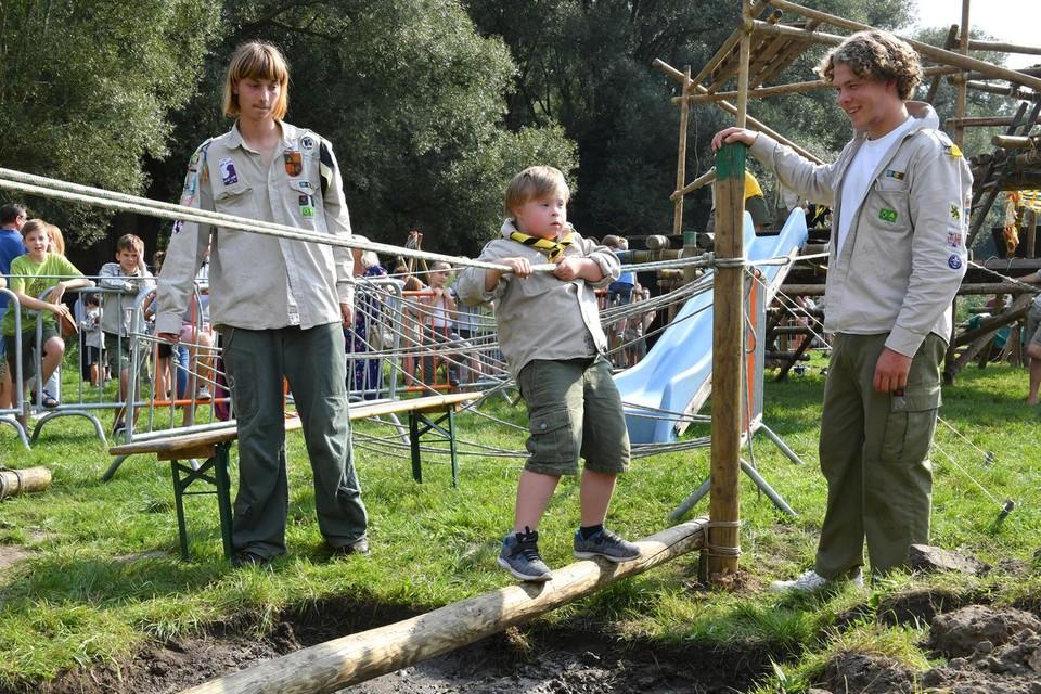 Ook kinderen met een beperking kunnen in Wijnegem beleven hoe tof het is om ene scout te zijn. Hier Lenne Paridaens die zich onder leiding van Dries Willems en Thibo Van Spitaels aan iets heel spannends.