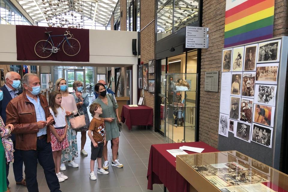 Oud-wielrenner Jos Jacobs (bruine vest) bekijkt samen met familie en vrienden in het gemeentehuis van Vosselaar de tentoonstelling over lokale wielerhelden.