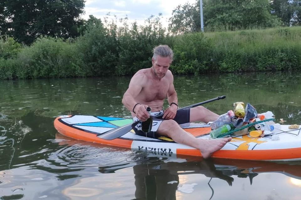 Dirk Van de Velde monstert een fles bubbels die hij uit het water vist.