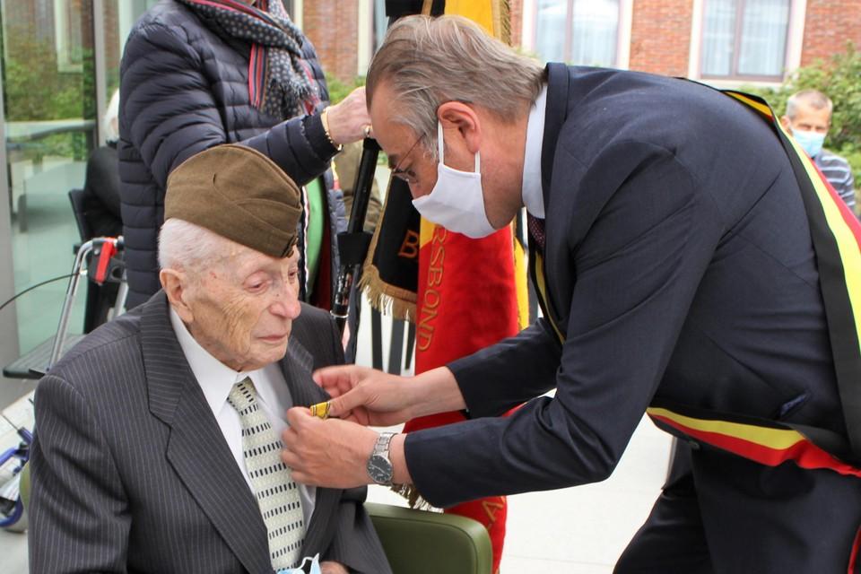 Burgemeester Walter Horemans spelde in mei het ereteken op bij Marcel Van den Broeck.
