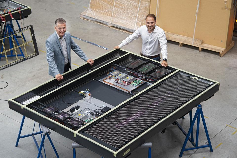 Directeur Dirk Geenen en Jeroen Raeijmaekers in de productie bij een bord voor parkeergeleiding in Turnhout.