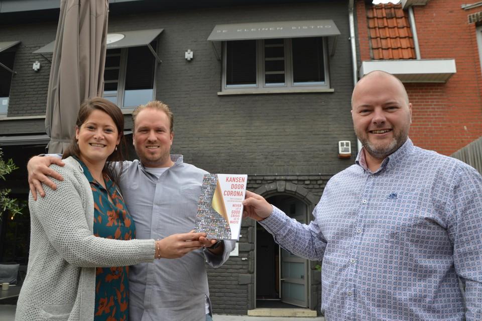 Gastvrouw Thari De Pooter en chef-kok Lawrence Elliott van De Kleinen Bistro krijgen het eerste exemplaar van co-auteur Tom Sleeuwaert.