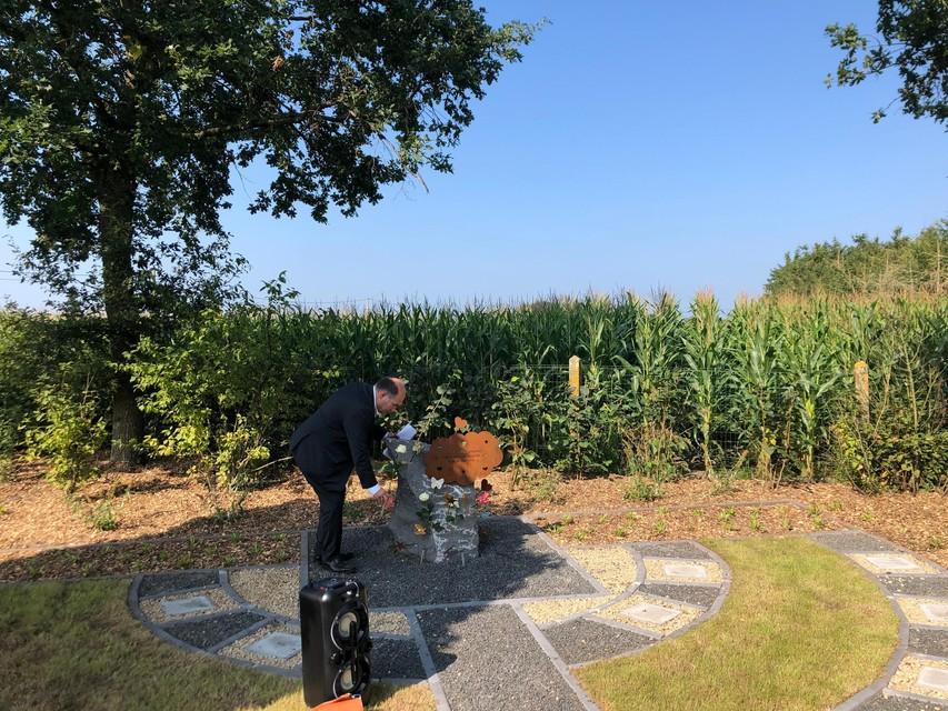 Burgemeester Bart Craane legt een witte roos bij het kunstwerk op de hartjesweide in Vlimmeren.