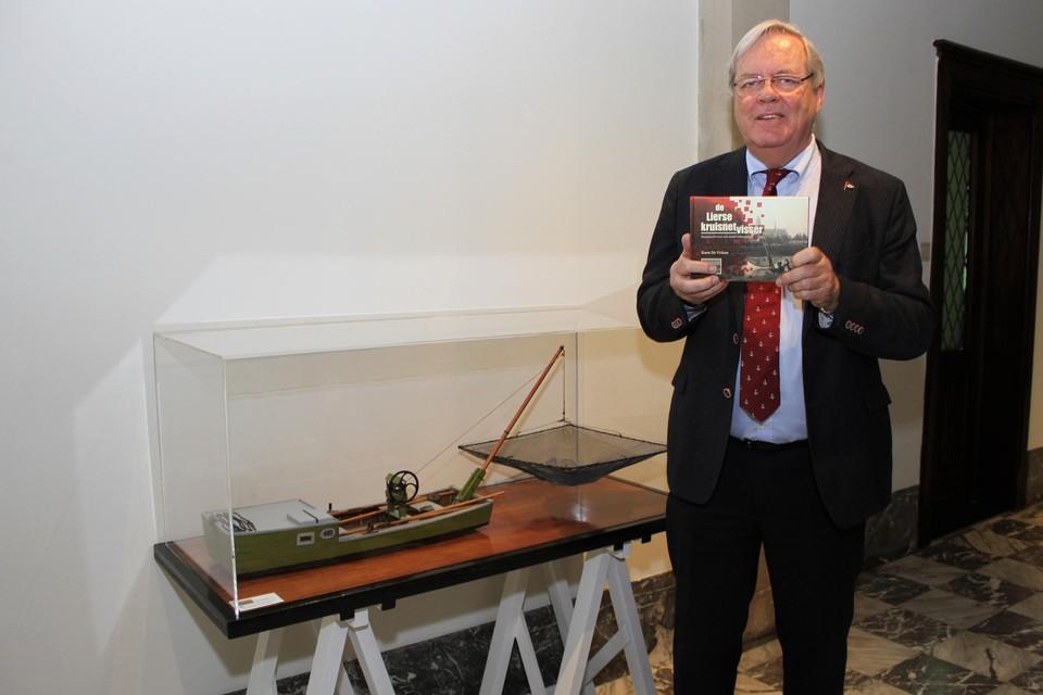 Koen De Vriese staat met zijn boek bij het model van een Lierse palingschuit, gebouwd door de School voor Scheepsmodelbouw.