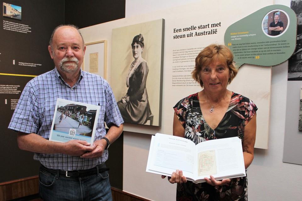 Auteurs Hugo De Bot en Greet Vervloet tonen het jubileumboek bij een van de infopanelen op de expo.