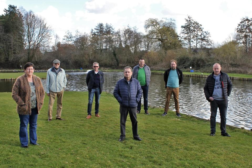 Ondervoorzitter Gust Bogaerts (derde van links) met andere (bestuurs)leden aan hun visput waarin drie ton vis zwemt.