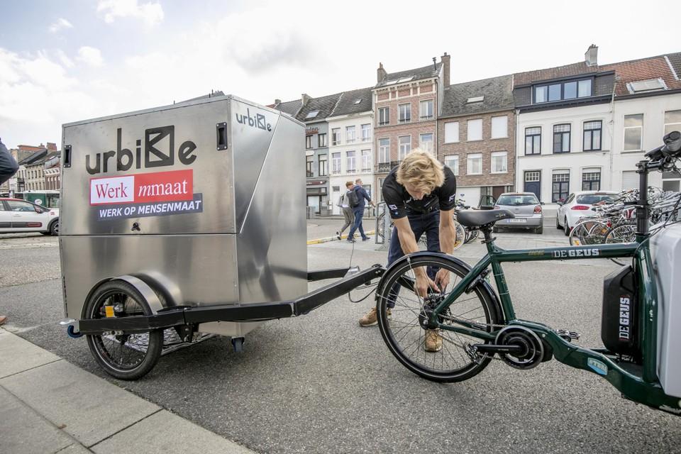 Een medewerker van Urbike bevestigt de boxcontainer aan de bakfiets van Werkmmaat.