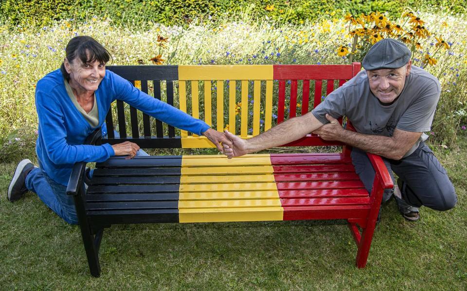 Piet en Wies bij hun opvallende tricolore bank.