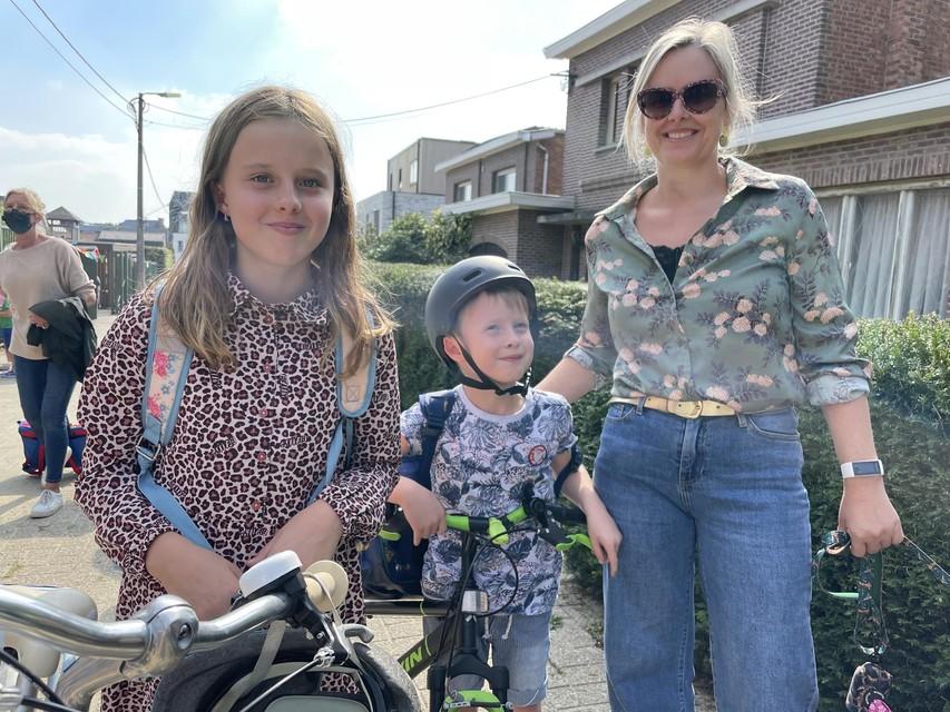 """Kim Lambrechts met Lola en Gus aan de schoolpoort in het Bergstraatje. """"We fietsen van hieruit richting Heiststeenweg, waar nog wel toezicht is."""""""