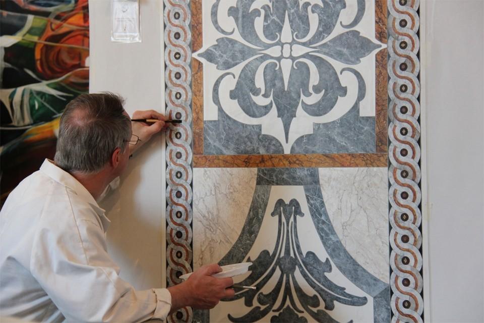 Jan schildert een imitatie van marmer-inlegwerk. Met een marterharen penseel bootst hij de adering van het marmer na.