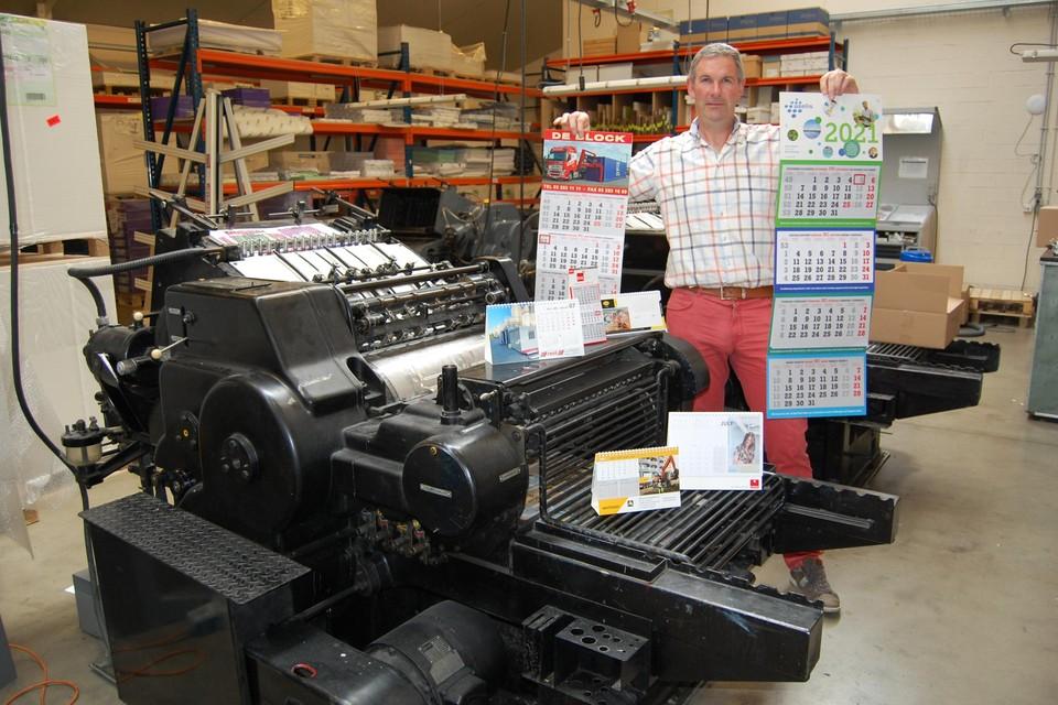 Zaakvoerder Marc Janssens bij een oude drukmachine met een hoop kalenders. Vorig jaar gingen er nog liefst 120.000 exemplaren de deur uit.