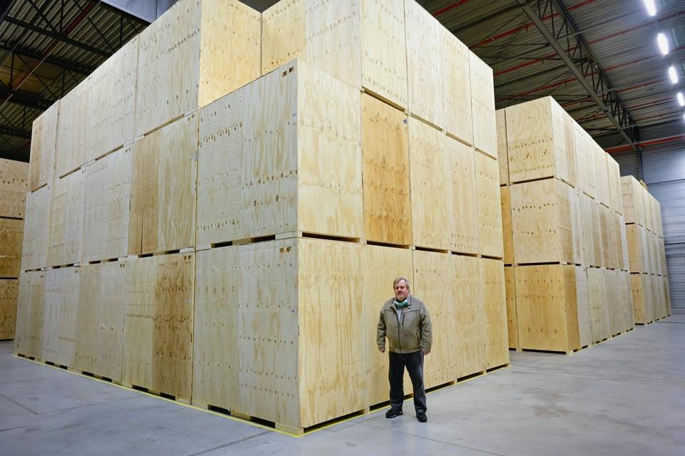 Henrik Rooms van Merak bij de houten bakken waarin de mondmaskers liggen opgeslagen.