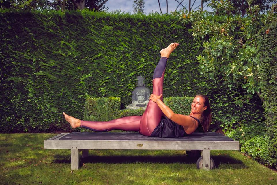 """Sylvie Komkommer in de tuin van haar villa Katy Cari, met minzaam grijnzend Boeddhabeeld in de haag: """"In Knokke sporten de mensen veel, meer dan in eender welke andere gemeente."""""""