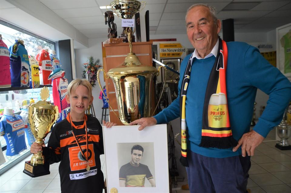 Jef Peeters (6) met zijn Belgische kampioensbeker en gouden medaille in het Kempens Wielermuseum naast opa Frans 'Suske' Verhaegen bij een portret van Frans als Belgisch kampioen bij de jeugd. De beker achter het portret won Frans in Valencia.