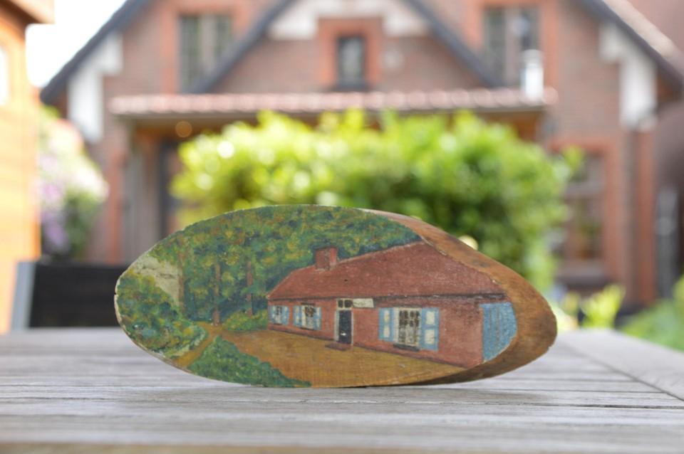 De beschilderde boomschijf die verstopt zat achter lood aan de schouw. Het koppel herkende er direct 't Boshuisje in, waar ze vlakbij wonen.