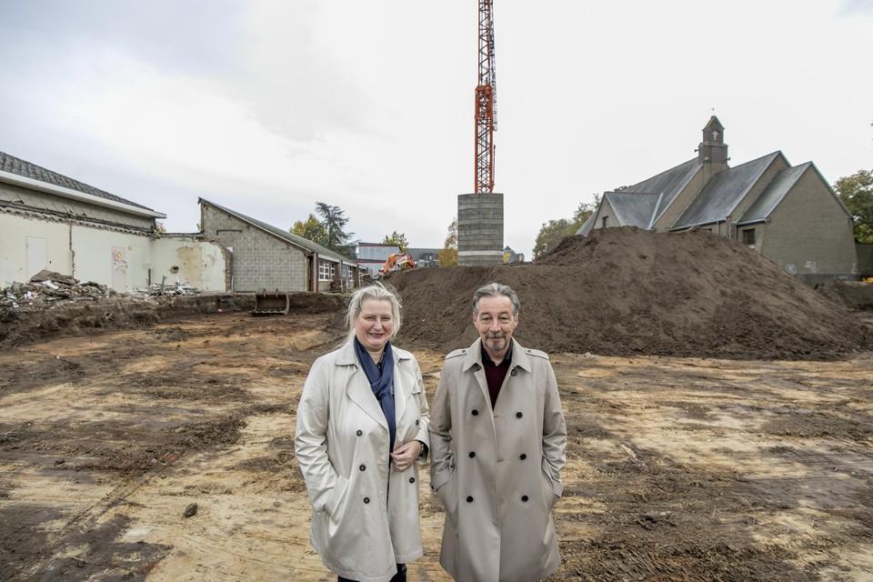 Directeurs Elly Van Kerckhoven en Erik De Ceuster staan op de werf, die loopt van het bestaande schoolgebouw aan de linkerkant tot de kerk aan de rechterkant.