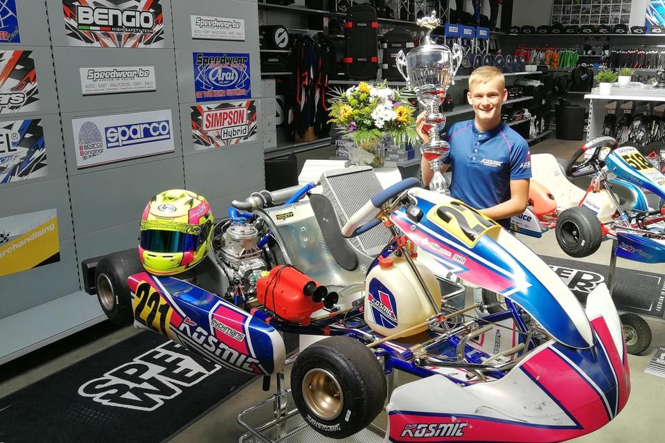 Ean Eyckmans toont trots zijn trofee van de derde plaats in de eindstand van het Europees Kampioenschap. Hij doet dat bij zijn kart in de winkel van zijn ouders in Herentals.