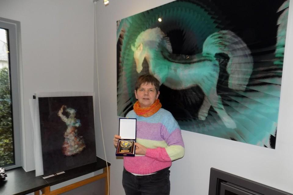 Kunstenares Anita Fleerackers uit Gierle toont haar gouden medaille bij twee van haar bekroonde digitale kunstwerken, Crazy Horse en Fun.